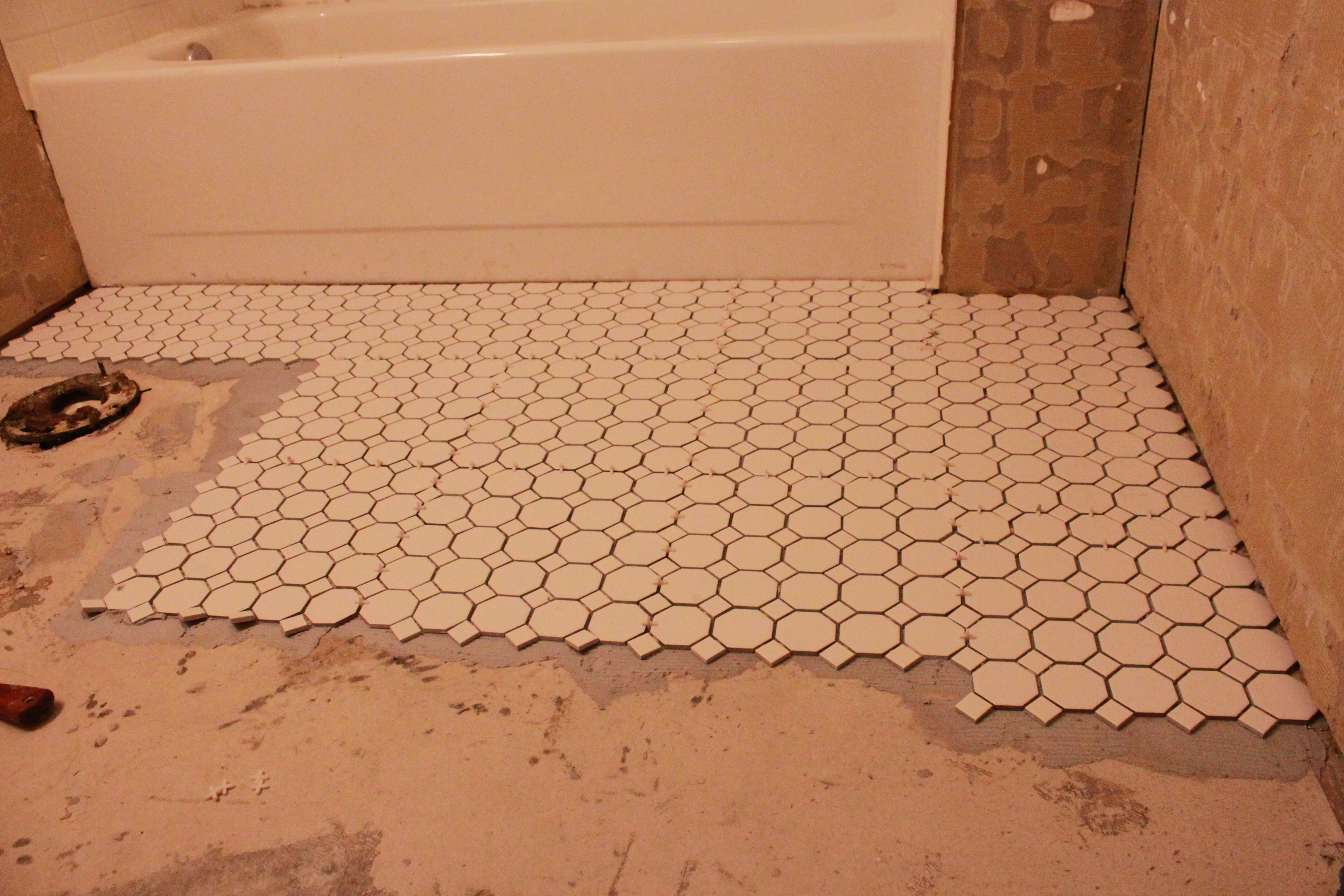 Guest bathroom reno tiling the floors all things new interiors spread your thin set with a trowel and use the notched side to get off any excess and make sure its level lay the tile and press firmly place spacers dailygadgetfo Gallery